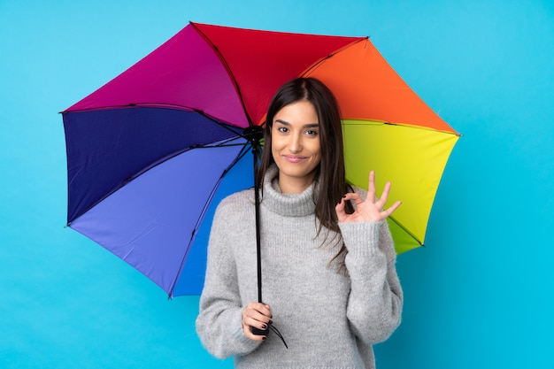 Young brunette woman holding an umbrella over isolated blue wall showing an ok sign with fingers