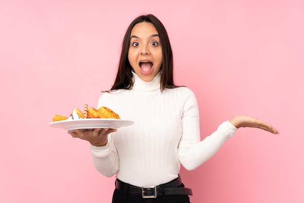 Young brunette woman holding waffles on isolated pink with shocked facial expression