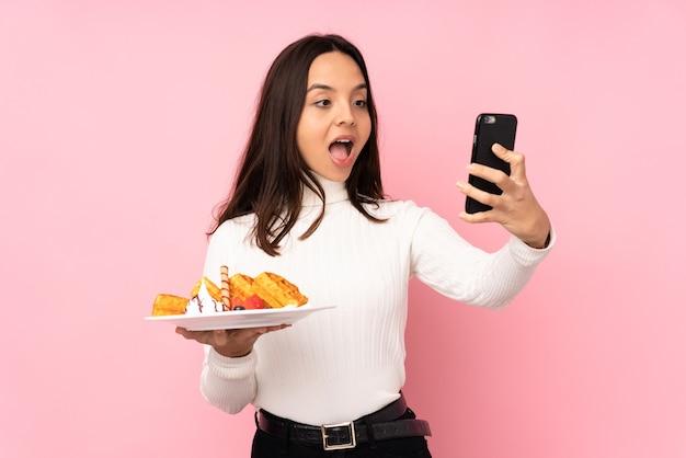 持ち帰り用のコーヒーと携帯電話を保持している孤立したピンクの背景の上にワッフルを保持している若いブルネットの女性