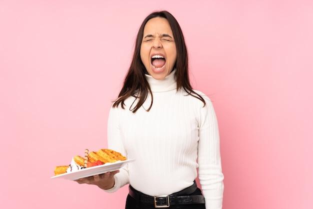 Молодая брюнетка женщина, держащая вафли на изолированном розовом фоне, кричит вперед с широко открытым ртом