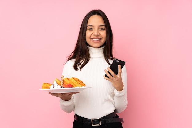 持ち帰り用のコーヒーと携帯電話を保持している孤立したピンクの壁にワッフルを保持している若いブルネットの女性