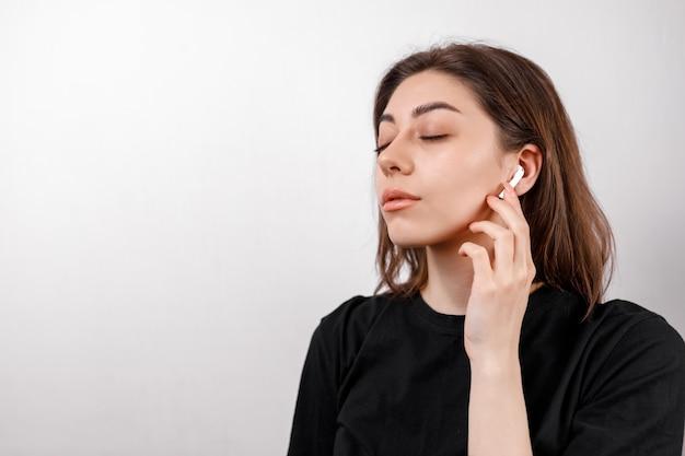 白地に黒のtシャツの若いブルネットの女性は分離された音楽を聴きます