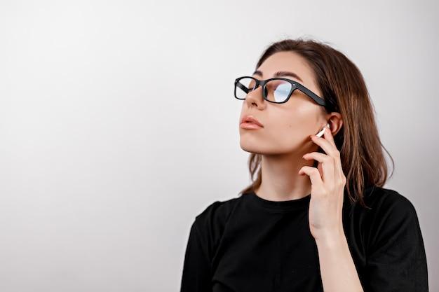 白地に黒のtシャツを着た若いブルネットの女性は、分離されたメガネで音楽を聴きます