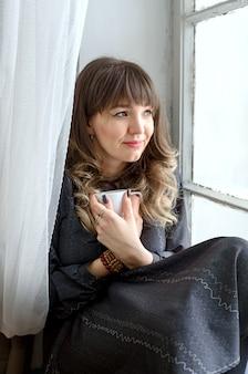Молодая брюнетка в платье мечтательно сидит у окна.