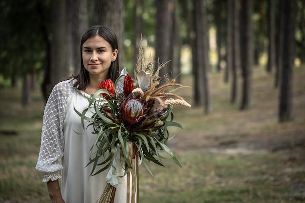ぼやけた背景、コピースペースに森の花の花束と白いドレスを着た若いブルネットの女性。