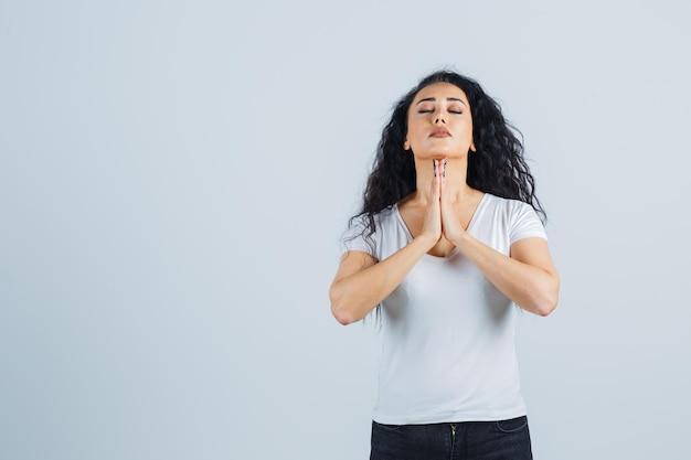 祈っている白いtシャツの若いブルネットの女性