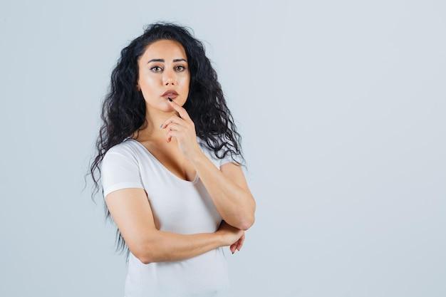 白いtシャツを着た若いブルネットの女性