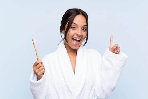 素晴らしいアイデアを指している分離の青い壁に彼女の歯を磨くバスローブの若いブルネットの女性