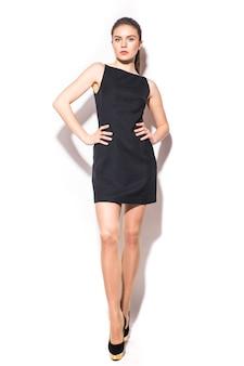 白い背景でポーズをとって黒いドレスの若いブルネットの女性