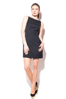 흰색 배경에 포즈 검은 드레스에 젊은 갈색 머리 여자