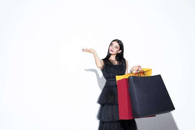 흰 벽에 쇼핑하는 검은 드레스에 젊은 갈색 머리 여자. 매력적인 백인 여성 모델.