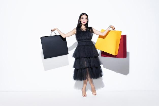 흰 벽에 쇼핑하는 검은 드레스에 젊은 갈색 머리 여자.