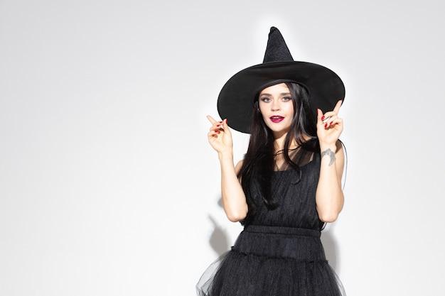 Молодая женщина брюнет в черной шляпе и костюме на белой предпосылке. привлекательная кавказская женская модель. хэллоуин, черная пятница, киберпонедельник, распродажи, осенняя концепция. copyspace. указывая вверх.