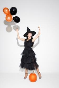 黒い帽子と白い背景の上の衣装で若いブルネットの女性。魅力的な白人女性モデル。ハロウィーン、ブラックフライデー、サイバーマンデー、販売、秋のコンセプト