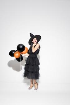 Молодая женщина брюнет в черной шляпе и костюме на белой предпосылке. привлекательная кавказская женская модель. хэллоуин, черная пятница, киберпонедельник, распродажи, осенняя концепция