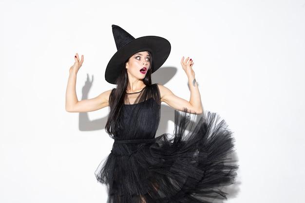 검은 모자와 흰색 바탕에 의상에서 젊은 갈색 머리 여자. 매력적인 백인 여성 모델. 할로윈, 검은 금요일, 사이버 월요일, 판매, 가을 개념