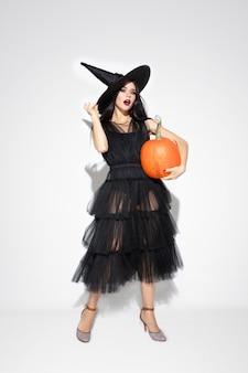검은 모자와 흰색 의상에서 젊은 갈색 머리 여자