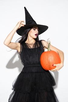 Молодая брюнетка женщина в черной шляпе и костюме на белом