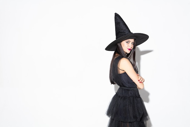 黒の帽子と白の衣装で若いブルネットの女性