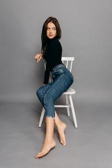 Молодая брюнетка женщина в черном сидит на стуле. красивая фотомодель с каштановыми волосами, изолированными на сером фоне. фото высокого качества