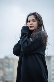 Молодая брюнетка женщина в черном свитере, стоя на открытом воздухе