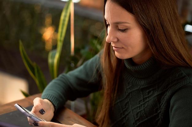 Молодая брюнетка женщина в кафе с ноутбуком общается с помощью смартфона крупным планом