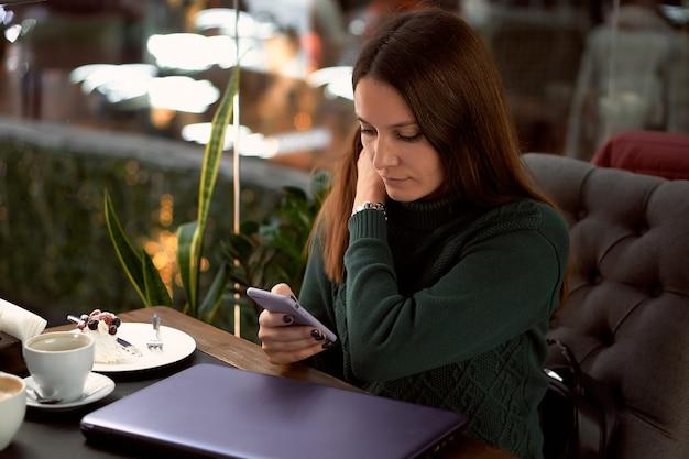 Молодая брюнетка женщина в кафе с ноутбуком общается с помощью смартфона