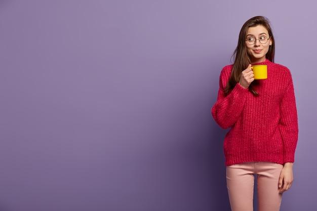 居心地の良い冬の服を着た若いブルネットの女性