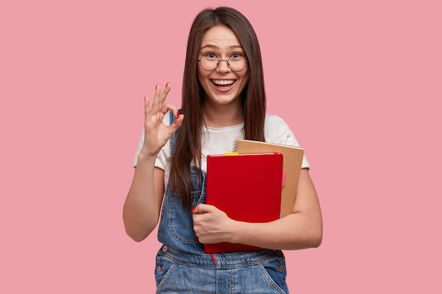 メモ帳を保持しているデニムのオーバーオールの若いブルネットの女性