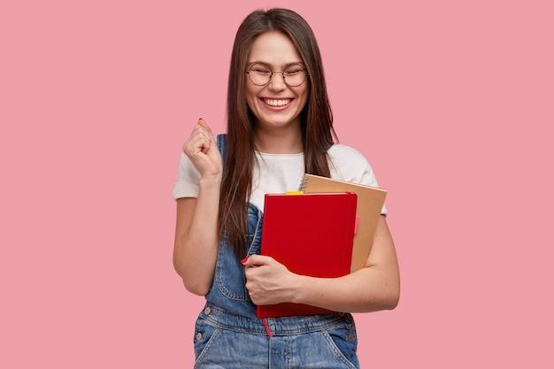 Молодая брюнетка женщина в джинсовом комбинезоне держит блокноты