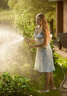 ホースパイプで裏庭で働くドレスを着た若いブルネットの女性