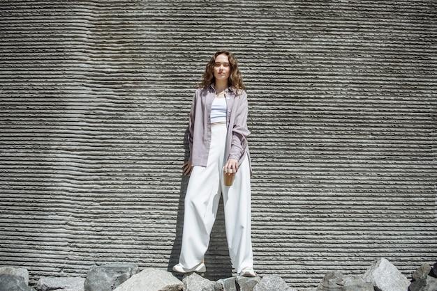 거리 의류 카탈로그에 있는 도시 벽의 배경에 포즈를 취한 세련된 현대적인 옷을 입은 젊은 브루네트 여성