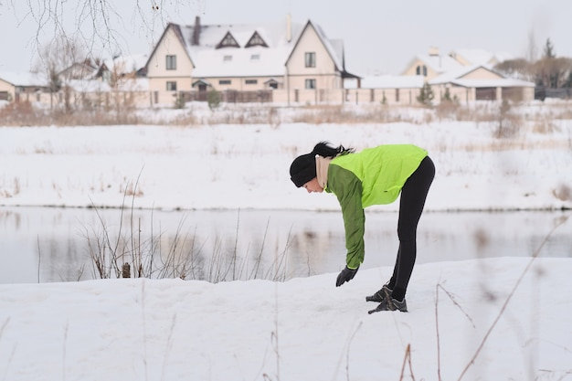 湖に立って、走る前に運動をしている緑のジャケットの若いブルネットの女性