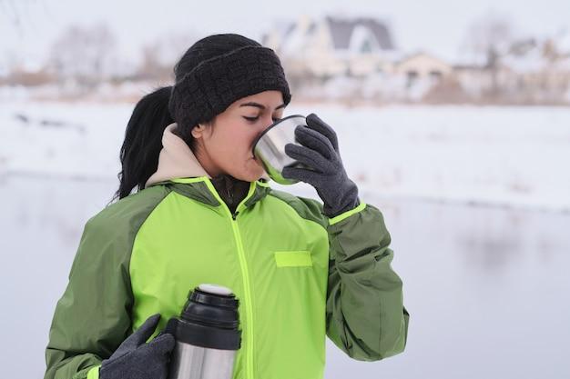 Молодая брюнетка в зеленой куртке стоит в зимнем парке и пьет горячий чай из чашки термоса