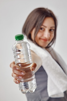 그녀의 목에 흰 수건을 들고 물 한 병을 보여주는 회색 tshirt에서 젊은 갈색 머리 여자