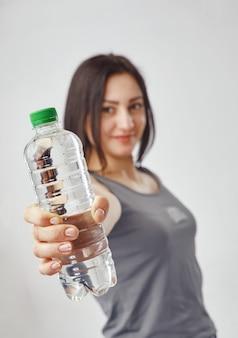 물 한 병을 보여주는 회색 tshirt에서 젊은 갈색 머리 여자