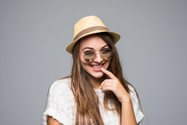 모자와 선글라스 회색에 웃 고있는 젊은 갈색 머리 여자