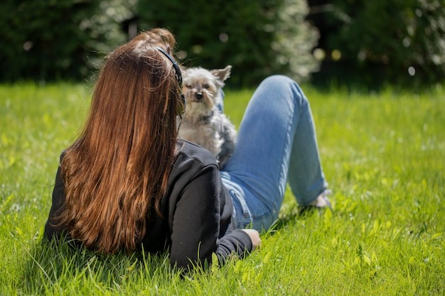 公園の芝生の上に横たわって、眺めを楽しんでいるペットの小さな犬と自然の中でリラックスしたヘッドフォンで若いブルネットの女性