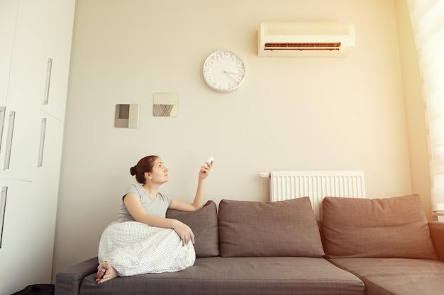 Молодая брюнетка женщина в своей современной квартире в гостиной. она включает кондиционер с пульта, сидя на диване. климат-контроль дома со сплит-системой, тонировка