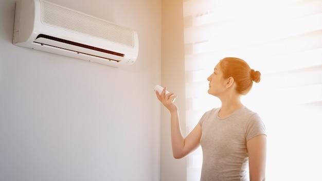 Молодая женщина брюнетки в ее современной квартире. она включает кондиционер с пульта дистанционного управления. климат-контроль дома со сплит-системой, солнечный свет