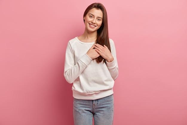 Молодая брюнетка женщина в джинсах и свитере