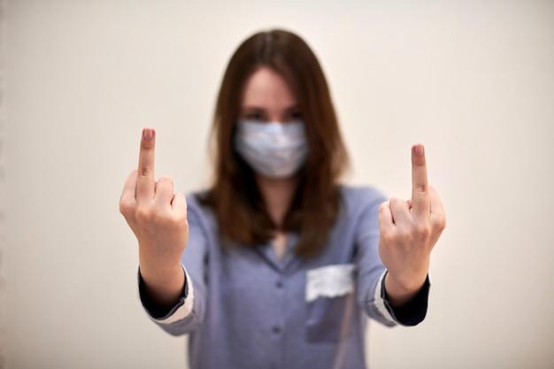 あなたのジェスチャーを性交を示す医療保護マスクの若いブルネットの女性。肖像画、ぼやけた顔