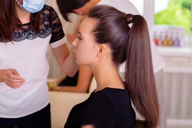 化粧の過程で若いブルネットの女性