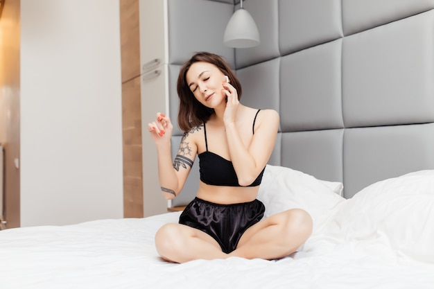 Молодая брюнетка в сексуальном нижнем белье, слушая музыку в наушниках на кровати