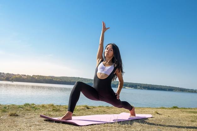 昼間近くの湖でのトレーニングの後、足を伸ばしているスポーツウェアの若いブルネットの女性。健康的な生活様式
