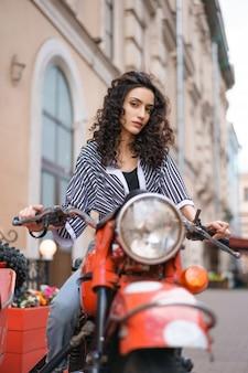 縞模様のシャツとジーンズの若いブルネットの女性は、屋外で赤いバイクに座っています。