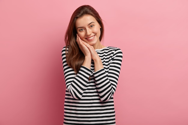 縞模様のシャツの若いブルネットの女性