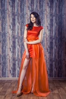 Молодая брюнетка женщина в стильном оранжевом шелковом платье позирует на деревянном фоне