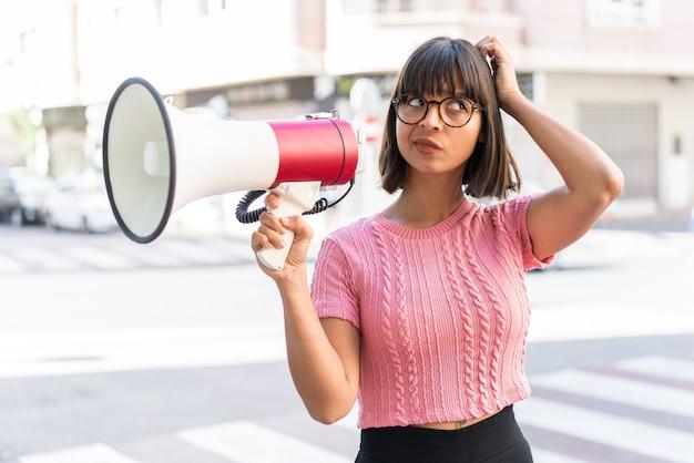 Молодая брюнетка женщина в городе держит мегафон и сомневается