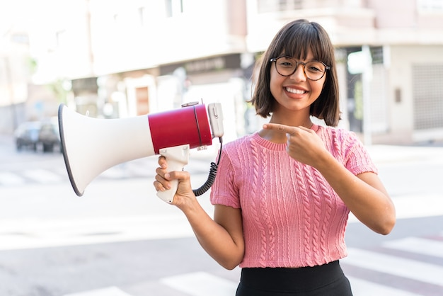 Молодая брюнетка женщина в городе держит мегафон и указывает сторону